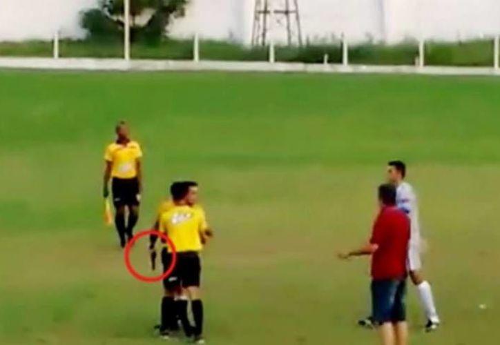 En imagen, el momento en el que el árbitro, con arma en mano, encara a una persona quien ingresó a la cancha momentos antes, esto en futbol amateur de Brasil. (Captura de pantalla de Youtube)