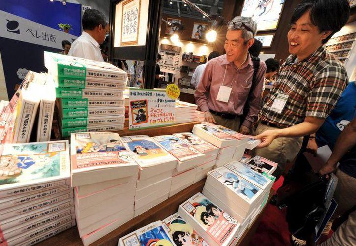 Dos hombres se interesan por las obras del artista de manga Osamu Tezuka durante la Feria Internacional de Libro de Tokio, Japón. (EFE)