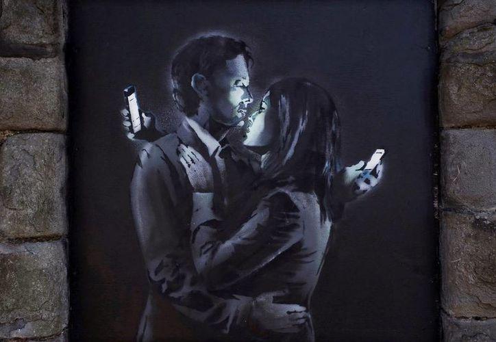 Imagen del mural 'Los amantes del móvil' muestra a un hombre y una mujer abrazándose mientras, cada uno, mira su teléfono móvil. (kommersant.ru)