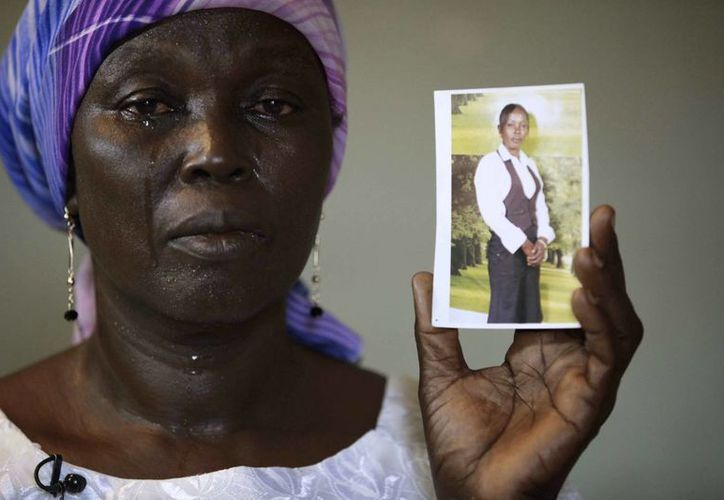 Una mujer llora mientras muestra la foto de su hija, una colegiala secuestrada en Chibok, Nigeria. (Agencias)
