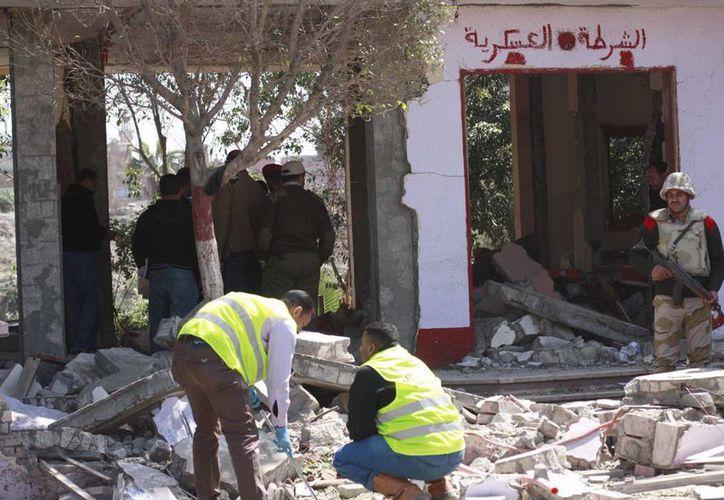 Unos agentes examinan los daños ocasionados por el ataque contra un cuartel militar registrado esta mañana en El Cairo. (EFE)