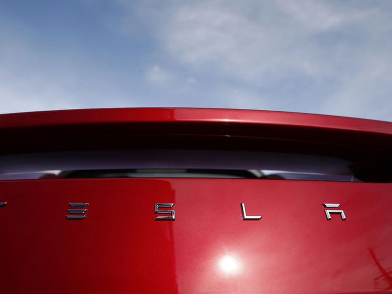 The sun shines off the rear deck of a roadster on a Tesla dealer's lot in the south Denver suburb of Littleton, Colo