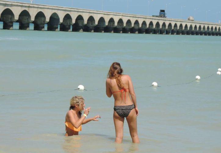 Dos jóvenes turistas extranjeras se bañan en Progreso teniendo como marco el muelle fiscal. (Manuel Pool/SIPSE)