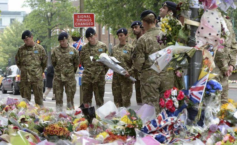 Soldados británicos visitan el lugar donde varios ciudadanos dejaron ramos de flores y mensajes en recuerdo del soldado británico Lee Rigby. (EFE)