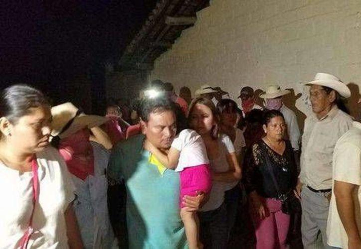 El ingeniero Isauro Paz Duque, quien carga a la niña de la falda rosa, se reunió con su familia. (Milenio)