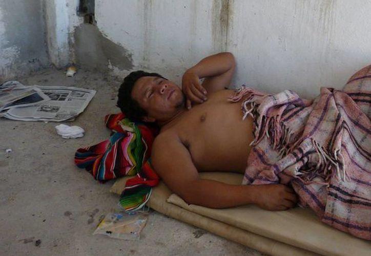 Él vive entre cartones, harapos y colchonetas, compartiendo el techo con otros indigentes. (Licety Díaz/SIPSE)