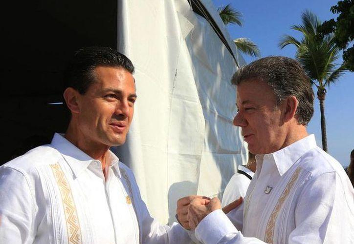 El presidente de Colombia, Juan Manuel Santos (der.), saluda a su par de México, Enrique Peña Nieto, en la IX Cumbre de la Alianza, en Nayarit. (Notimex)