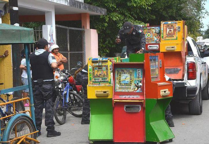 Elementos federales decomisaron varios minicasinos en Hunucmá. Imagen del momento en que federales cargaban los aparatos para llevárselos del lugar. (Milenio Novedades)