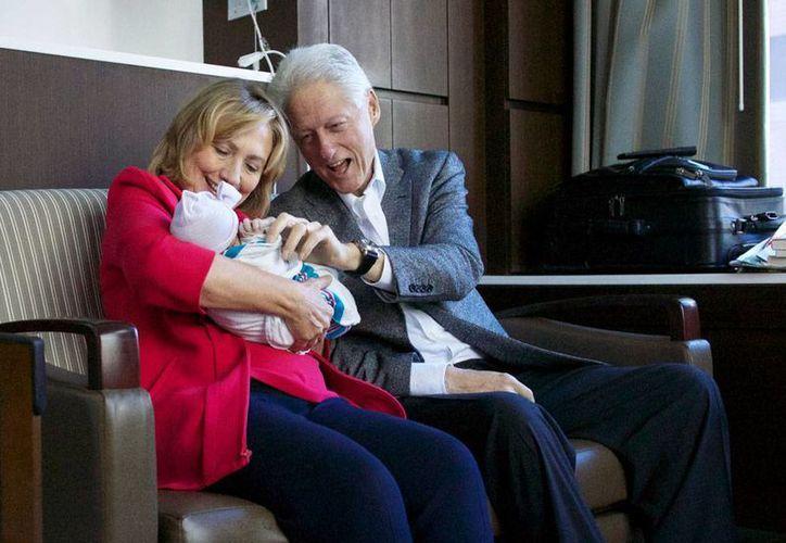 Los orgullosos abuelos, el exnúmero de EU, Bill Clinton, y la exnúmero 2 de la Unión Americana, Hilary, con su nieta Charlotte Mezvinsky. (AP)
