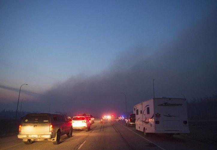Miles de habitantes de  Fort McMurray, Canadá, han desalojado la ciudad en interminables caravanas de vehículos desde los que observaron un panorama sombrío de vecindarios incendiados. (AP)