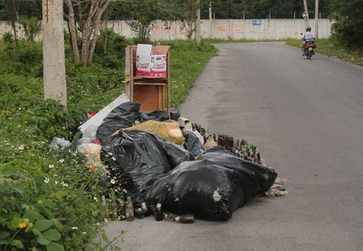 A pesar del letrero que prohíbe tirar basura en este sitio, ayer había desechos. (Gustavo Villegas/SIPSE)