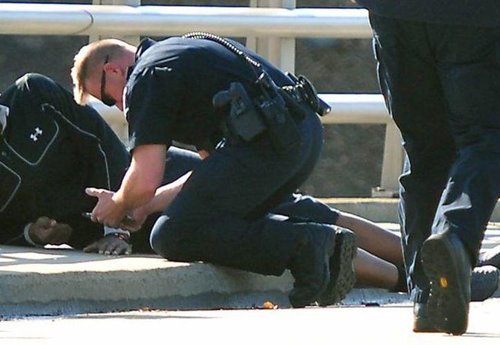 Un policía de Charlotte, Carolina del Norte, asiste al quarterback de los Panthers de Carolina Cam Newton tras un accidente automovilístico. (Foto AP/The Charlotte Observer, Todd Sumlin)