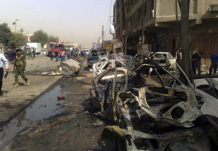 Varios coches dañados en el lugar donde explotó una bomba en el barrio de Al Karrada, en el centro de Bagdad, Irak. (Archivo/EFE)