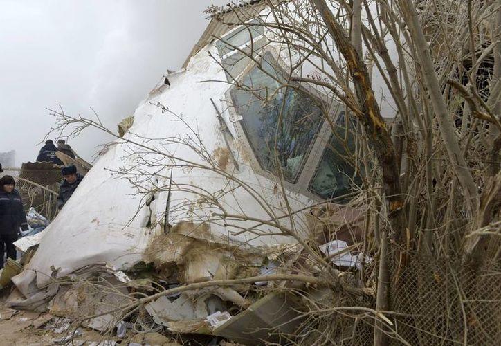 Funcionarios del Ministerio de Emergencias de Kirguistán inspeccionan parte de la cabina de un Boeing 747 de mercancías turco que se estrelló en una zona residencial en las afueras de la capital de Kirguistán, Bishkek. (AP/Vladimir Voronin)