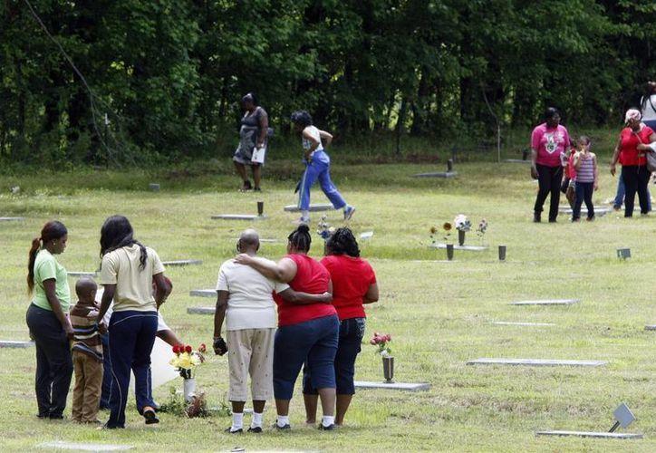 Imagen de varias personas reunidas frente a una tumba en el cementerio Galilee de Memphis, Tennessee. El cementerio ha sido acusado de numerosas irregularidades. (AP Photo/Karen Pulfer Focht).