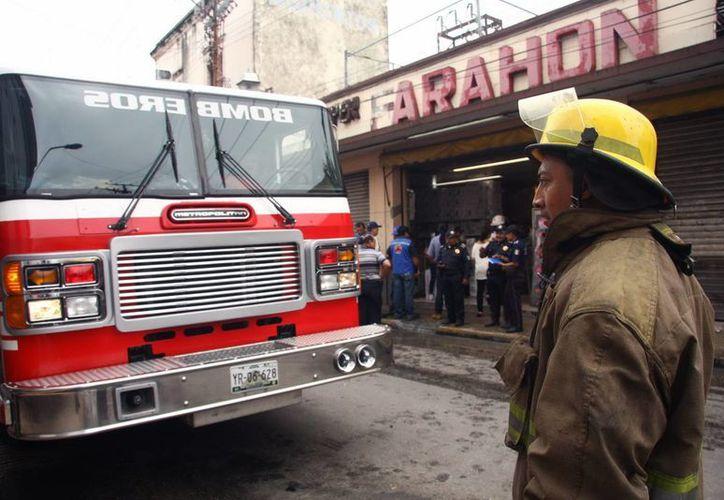 Un bombero observa la acción de sus compañeros durante el siniestro en el centro de Mérida. (Milenio Novedades)