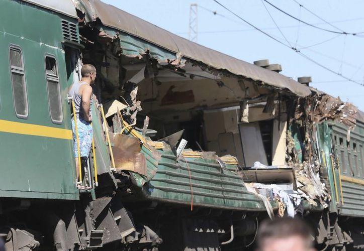 Varios miembros de un equipo de emergencias examinan los daños de un tren tras un accidente entre dos ferrocarriles, en Naro-Fominsk, Rusia. (EFE)
