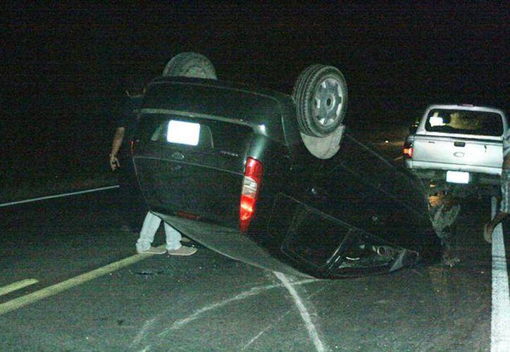 En el accidente ocurrido cerca del entronque a Acanceh, el auto Ford Fiesta quedó con las llantas hacia arriba. (Milenio Novedades)