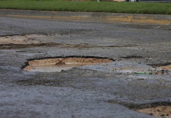 Con las lluvias del pasado mes de mayo, los baches volvieron a aparecer, y en la actualidad representan un serio problema para los conductores. (Harold Alcocer/SIPSE)