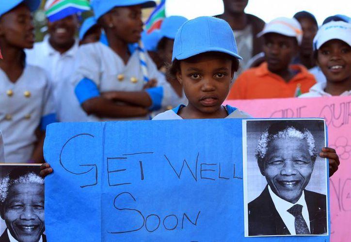 Niños africanos sostiene pósters y mensajes de apoyo a Mandela. (Agencias)