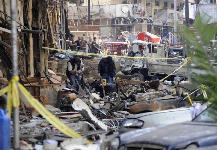 Un grupo de agentes de policía inspecciona varios coches dañados por una explosión en el sur de Beirut, el pasado viernes. (EFE)