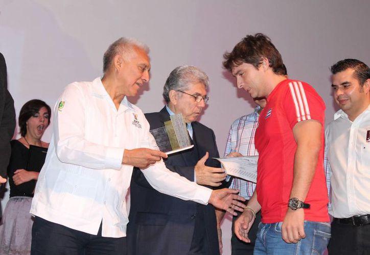 El cubano Lázaro Bruzón recibe el reconocimiento que lo acredita como campeón 2014 del Carlos Torre. (Milenio Novedades)
