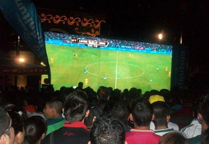 Los ojos de los aficionados al futbol estarán hoy por la tarde puestos sobre alguna pantalla de televisión para observar la final-final América-León. En la imagen, leoneses observaron en una pantalla gigante el partido de ida. (Notimex)
