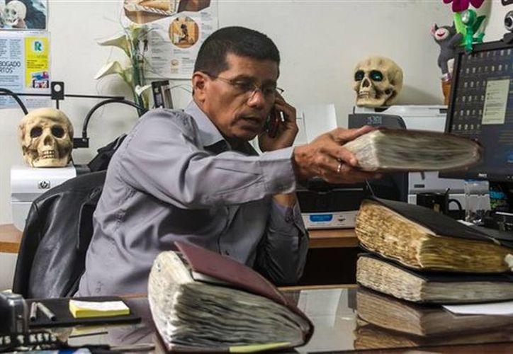 El criminólogo Israel Ticas habla por teléfono mientras acomoda sus libretas de notas en su oficina en San Salvador, El Salvador. (AP)