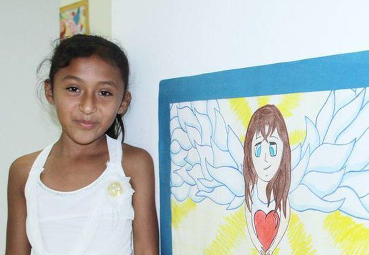 """Merary Azmirain Ortiz Chay posó al lado de su trabajo titulado """"La donación de órganos es una luz que ilumina muchas vidas"""". (Milenio Novedades)"""