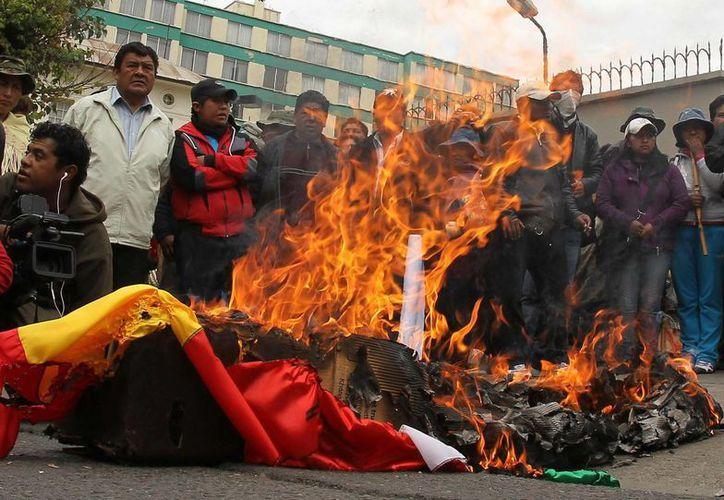 Seguidores del presidente de Bolivia, Evo Morales, queman las banderas de España y Portugal ante la embajada de E.U. de La Paz. (EFE)