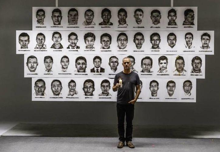 Steven Spazuk posa junto al mural en el que se ven los rostros de los 43 normalistas de Ayotzinapa que desaparecieron en septiembre de 2014 en Iguala, Guerrero. (Amnistía Internacional España)