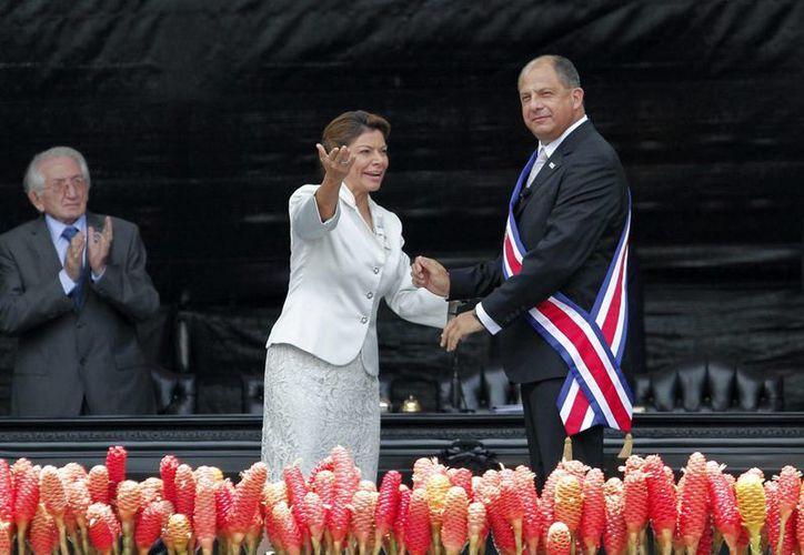 Luis Guillermo Solís (d), tras recibir la banda presidencial, junto a su antecesora, Laura Chinchilla (c), en San José, Costa Rica. (EFE)