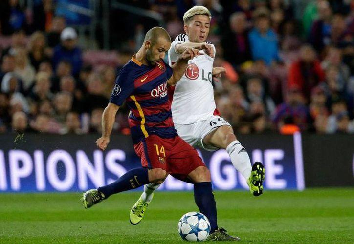 Javier Mascherano (14), jugador del Barcelona FC, está en la mira de la justicia, por evasión de impuestos. (Archivo/AP)