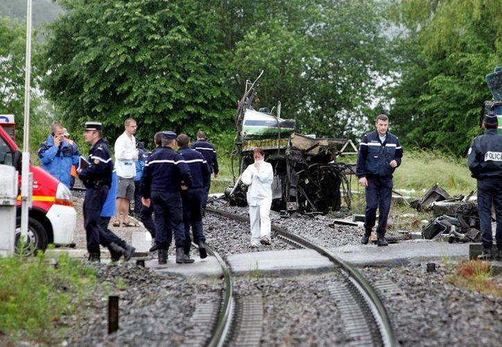 Policías, bomberos y rescatistas trabajan en el lugar donde un tren chocó contra un autobús escolar en Mesinges, cerca de Thonon-les-Bains, en los Alpes franceses, en 2008. (EFE/Archivo)