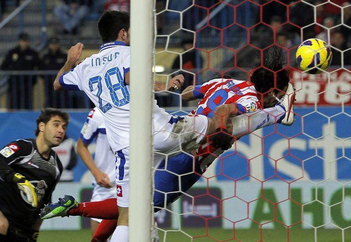 Falcao anota uno de sus goles pero recibe una patada de Insúa, del Deportivo La Coruña. (Agencias)