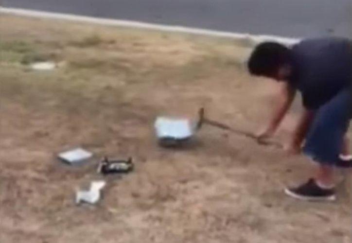 Imagen del momento en que Jason golpea con un martillo uno de sus dos juegos de Xbox como castigo por reprobar materias en la escuela. (Captura de pantalla de Youtube)