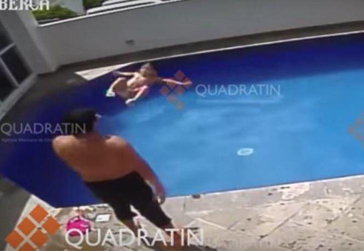 Uno de los momentos en que un sujeto lanza a una niña que no sabe nadar a la alberca; la acción la repitió en varias ocasiones. (Captura de pantalla/YouTube)