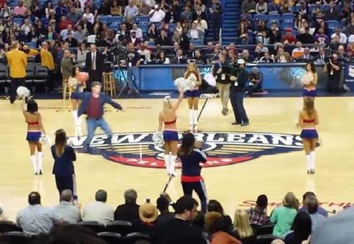 Momento exacto en el que Will Ferrel tira al suelo a una porrista de la NBA en el entre tiempo de un partido. (Captura de pantalla de YouTube)