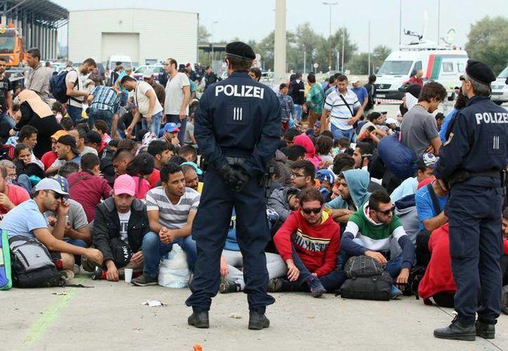 La policía austriaca observa a refugiados después de cruzar la frontera entre Hungría y Austria. (Agencias)