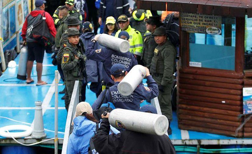 Bomberos, socorristas y buzos comenzaron el lunes labores de búsqueda y rescate de 16 personas desaparecidas en el naufragio de Colombia. (AP).