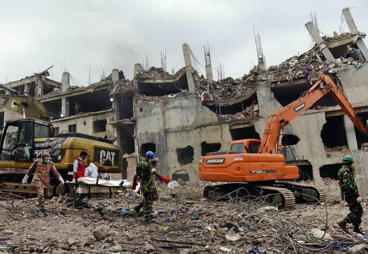 Rescatistas sacan un cadáver de los escombros de un edificio que se derrumbó, en Bangladesh, en abril pasado. Las víctimas mortales superan las 900. (Agencias)