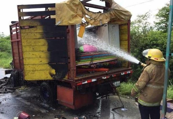 Un bombero sofoca el incendio en el camión de juegos mecánicos, en la carretera Mérida-Progreso. (Óscar Pérez/SIPSE)