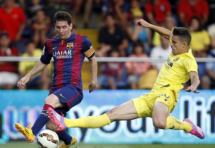 Lionel Messi (i) sufrió de un problema muscular en el partido Barcelona - Villarreal por la liga española. (AP)