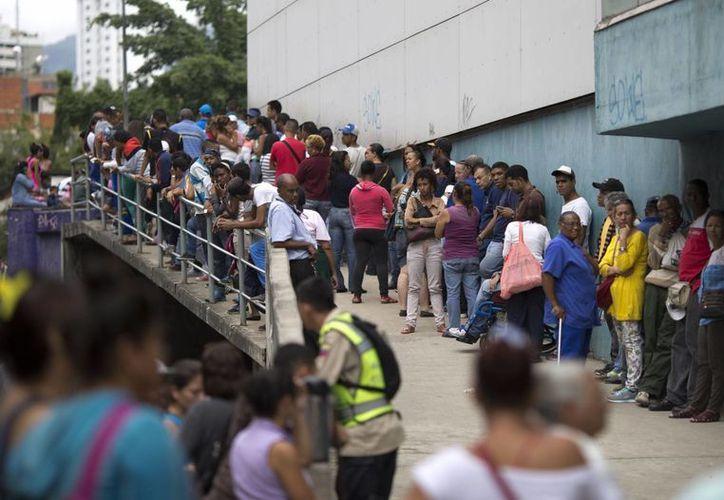 Imagen del 18 de noviembre de 2016 que muestra a la gente haciendo fila para entrar a un supermercado en Caracas, Venezuela. Una grave crisis económica golpea a esta nación sudamericana. (AP Photo/Ariana Cubillos)