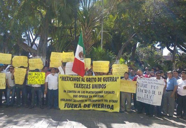 Taxistas se manifestaron este miércoles en Palacio de Gobierno para que se sancione a las empresas que, sin estar registradas, otorgan servicio de transporte contratado a través de plataformas tecnológicas. (Foto: Pallota/SIPSE)