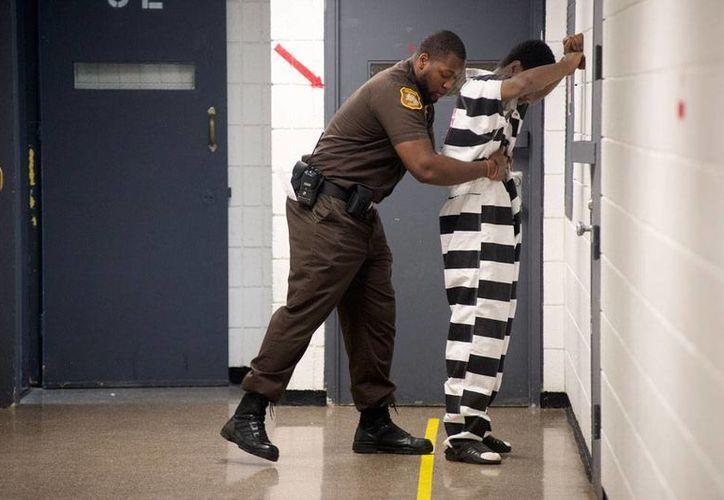El oficial  Terence Moore cachea a un interno antes de que éste se reúna con su abogado en la cárcel del condado Saginaw el viernes 18 de julio de 2014 en Saginaw, Michigan. (Foto de AP/The Saginaw News/MLive.com, Jeff Schrier)