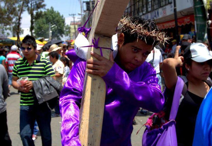 Con una cruz a cuestas, un joven realiza el recorrido del Cristo de Iztapalapa. Cada año cientos de vecinos de esa demarcación capitalina cumplen mandas en estas fechas. (Notimex)