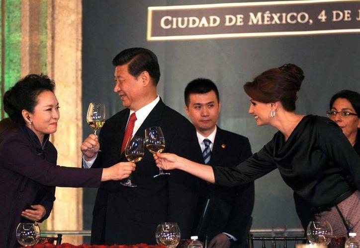 Peng Liyuan (i) brinda con Angélica Rivera, en cena de los presidentes de México y China con sus esposas. (Notimex)