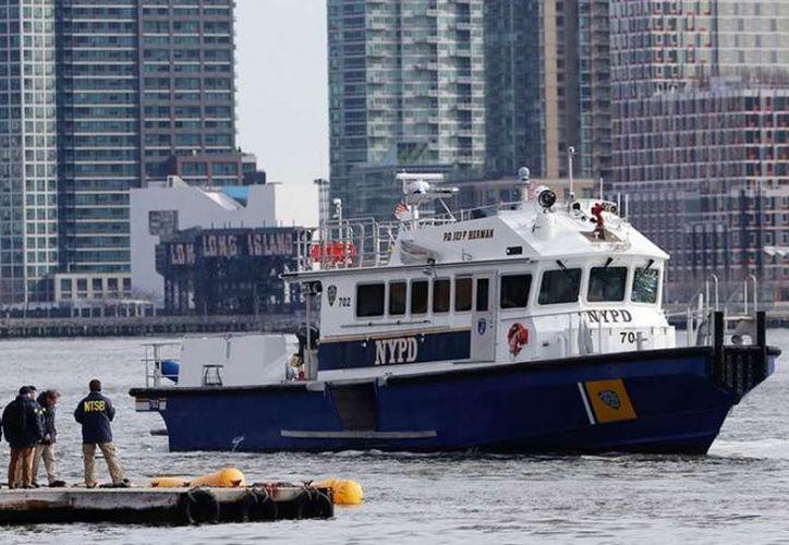 Un bote remolque privado rescató al piloto de las gélidas aguas del río Este. (AP)