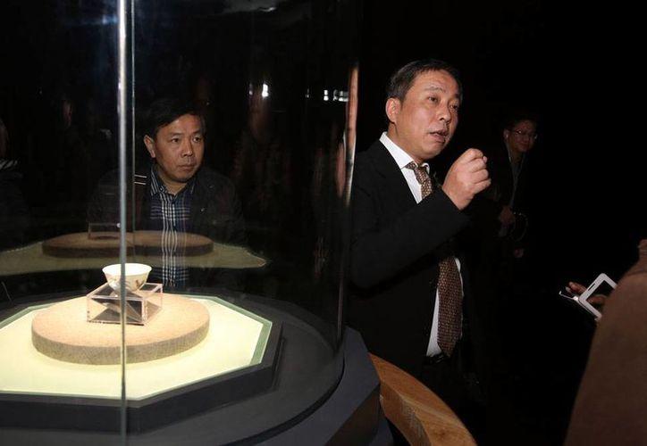 El coleccionista de arte y millonario chino Liu Yiqian habla en la inauguración de la exhibición de una taza de té de la Dinastía Ming valuada en 36 millones y que él compró con su tarjeta American Express, el 18 de diciembre de 2014, en Shanghai, China. (Chinatopix via AP)